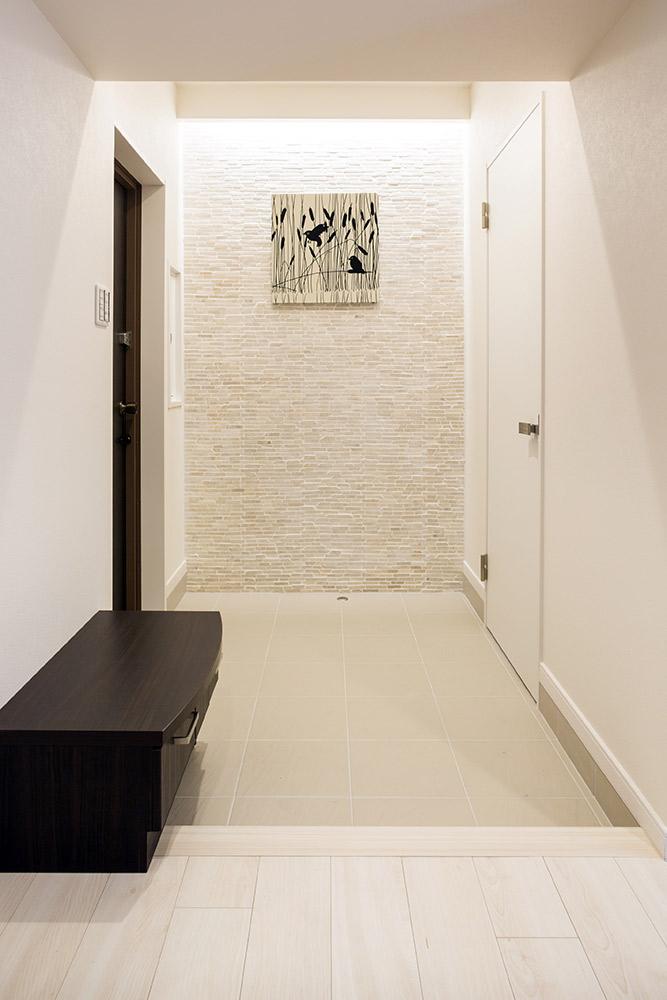 玄関横の石貼りを照らす間接照明の壁空間がお客様を出迎えます。