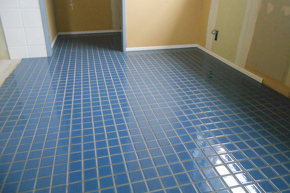 キッチン床は紺色の美しい艶のあるタイル仕上。防かび・防汚の目地材を使っています。