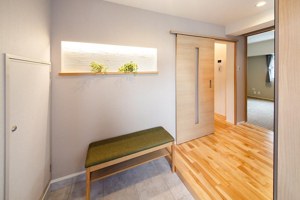 珪藻土塗・間接照明のニッチがある玄関には、立ち座りが楽なベンチを設置。