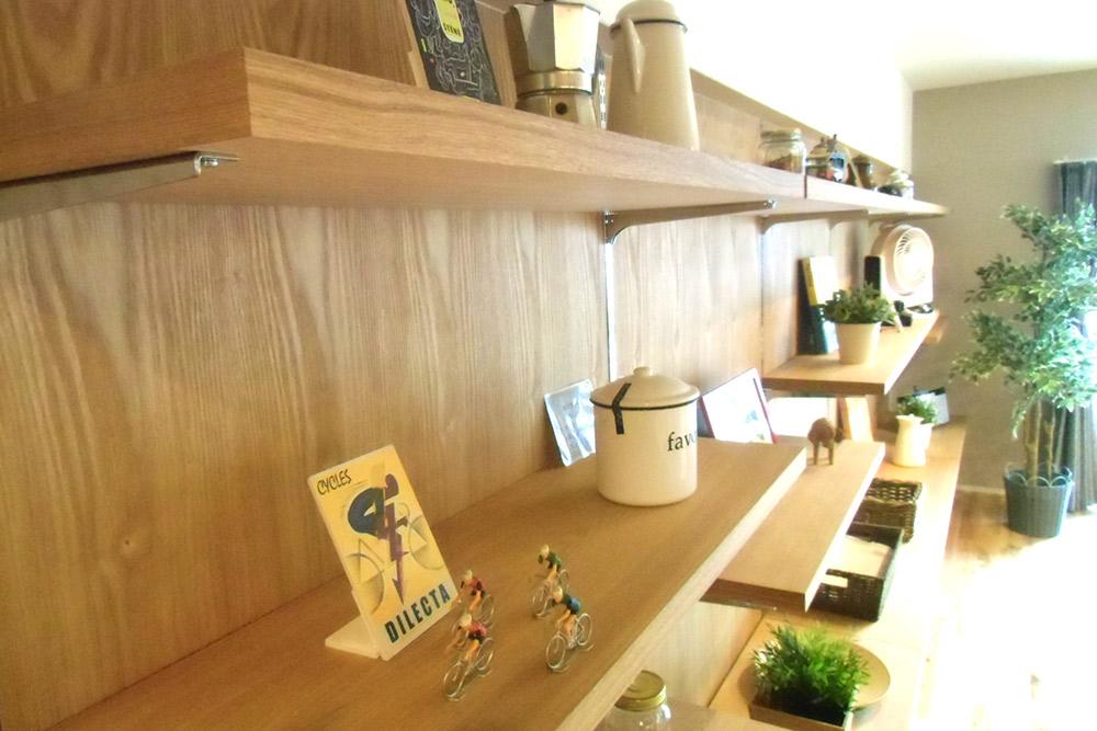 壁に突板を貼り、自在に高さを変えられる棚を設置。「見せる収納」が生活を彩ります。