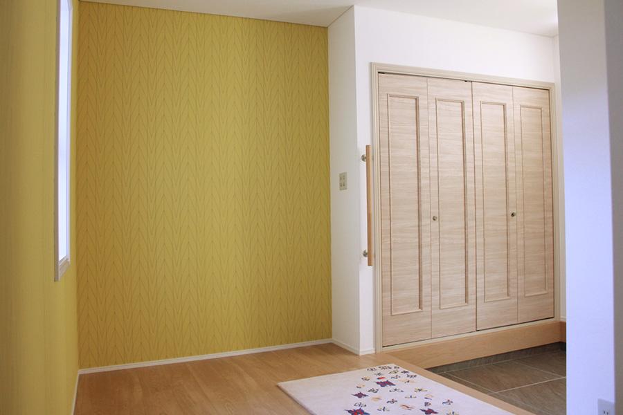 玄関ホールは既存の建具に、木目シートを貼り、雰囲気を変えています。玄関入って正面側の壁をモダンな黄色のクロスに貼り替え、フレッシュな印象で出迎えるスペースに。玄関床タイルを落ち着いた色彩にし、壁のビビッドさと調和を取れるようにしています。