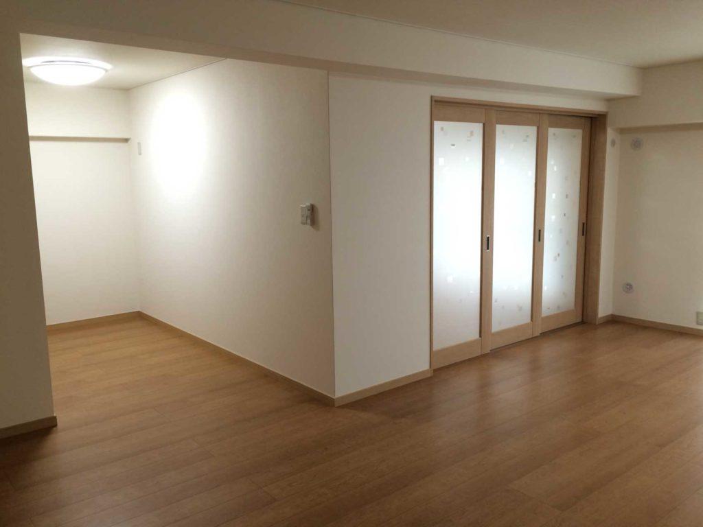 和室を洋室に変更し、出入口にガラス入りの三連引き戸を取付けることで、空間を広く使えるようにしました。