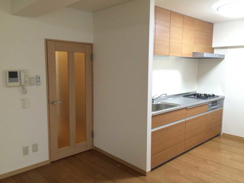 システムキッチンはフローリングと同色で明るくし、壁面もキッチンパネルを貼りお掃除もしやすくなりました。