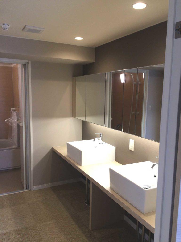 洗面台はお客様のご要望により、幅の広い天板に洗面ボウルを2台設置し壁面の収納棚に間接照明を取付け雰囲気のある空間にしました。