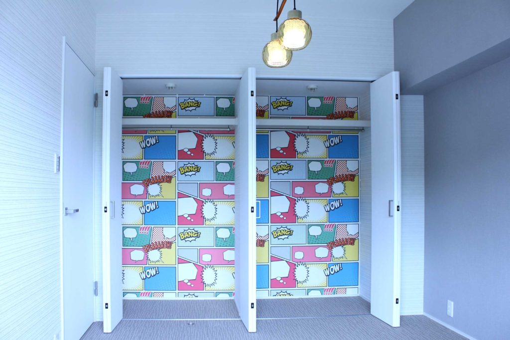 寝室は全体的に落ち着いた雰囲気のモノトーンのクロスに同色のタイルカーペット敷き。グローゼットの中は奥様のセレクトでアメコミ風のイラストのクロスを貼りました。