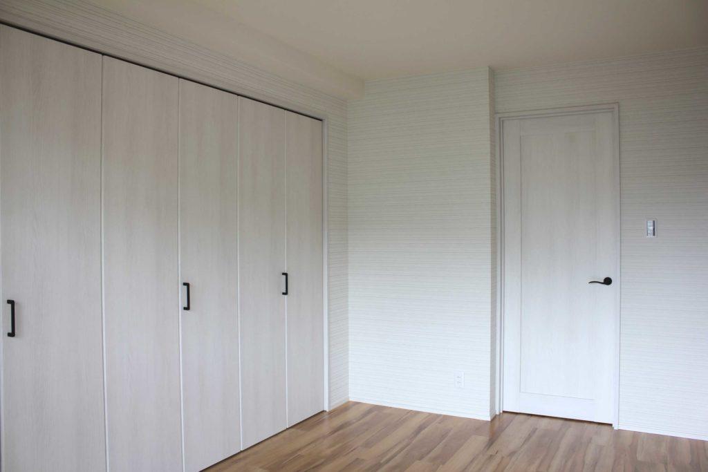 寝室には大きなクローゼットを設置。白の木調建具に落ち着いたグレー系の壁紙をコーディネートしました。