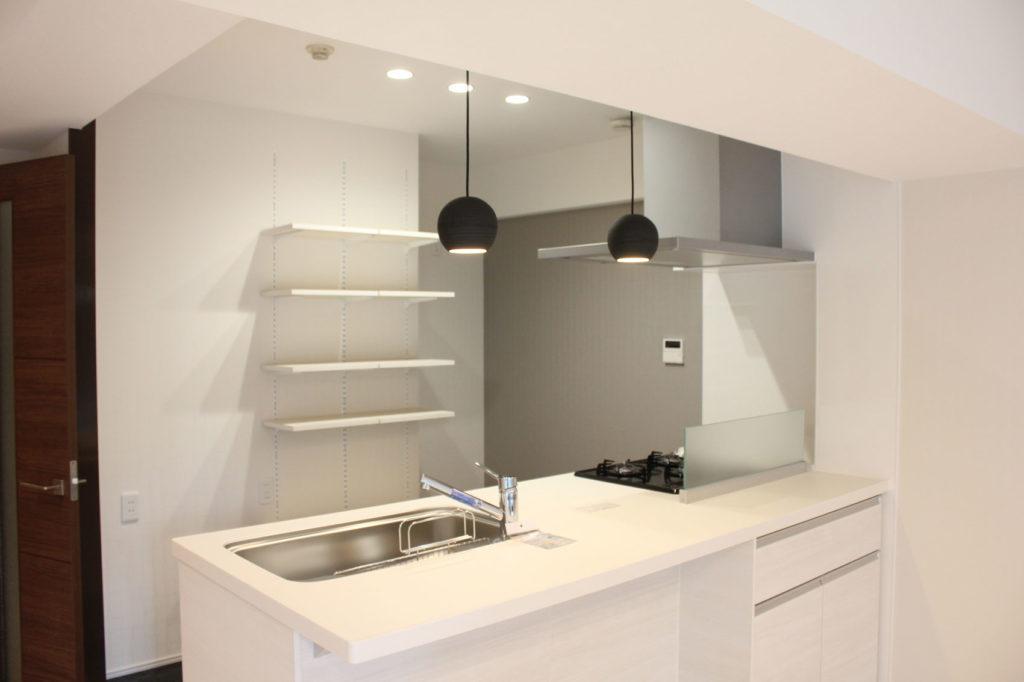 キッチンの背面に可動棚を設置。キッチンカウンター上部には陶器製のペンダントライトを取り付けモダンな空間を演出しました。