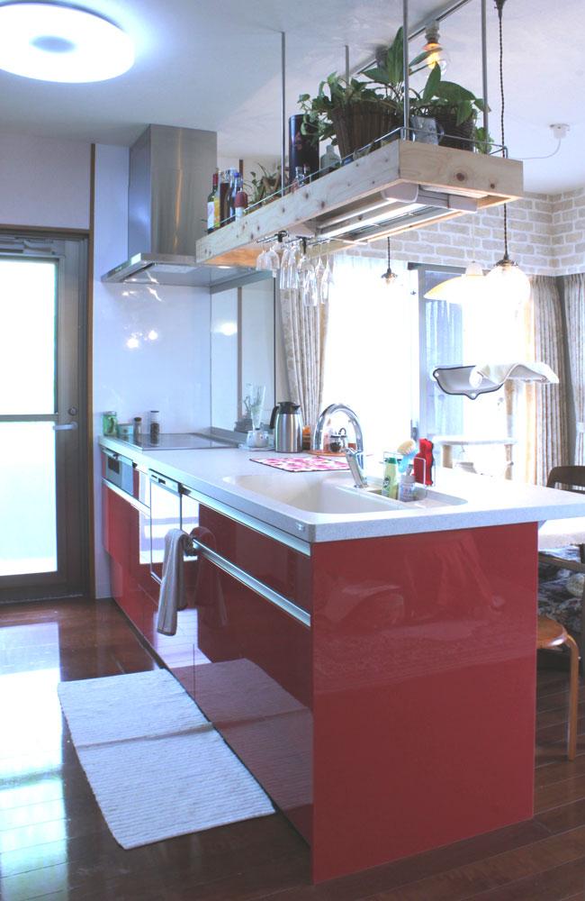 シックなボルドー色の扉に、天板は人工大理石の対面キッチンを設置しました。