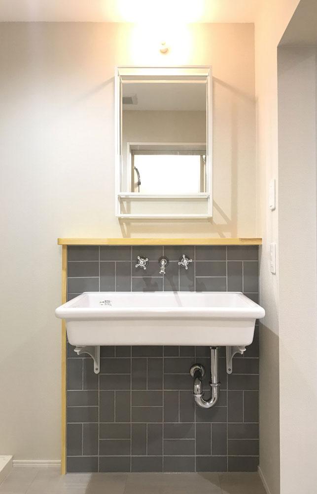 洗面は使い勝手の良い大きな実験シンクとイタリア製の水栓金具、グレーのタイルでコーディネート。