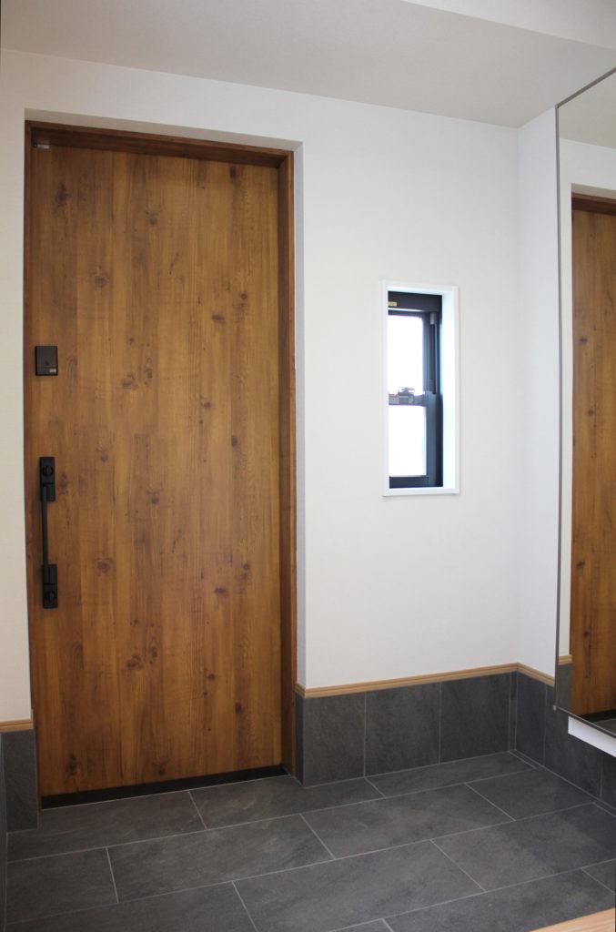 玄関戸に引戸が採用され、ダークグレーの玄関タイルが敷かれました。通風のための上げ下げ窓も設置されたことで玄関がより明るい印象になりました。