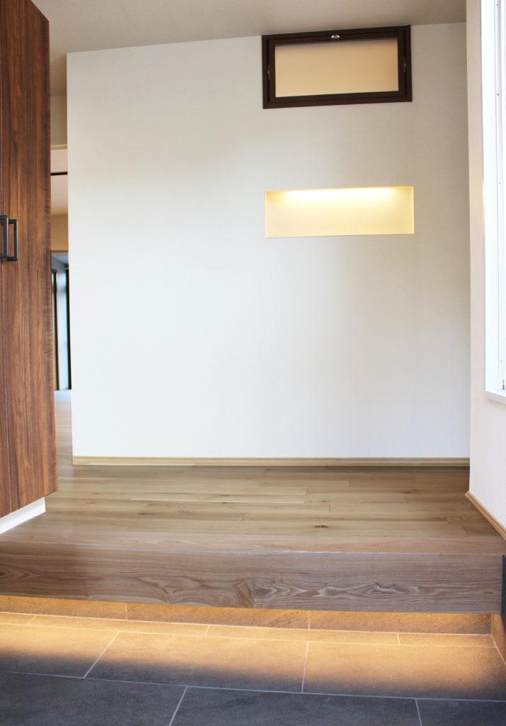 玄関には新しくシューズ収納やリビングと繋がる室内窓を設置。上り框とニッチには間接照明を取り付けました。