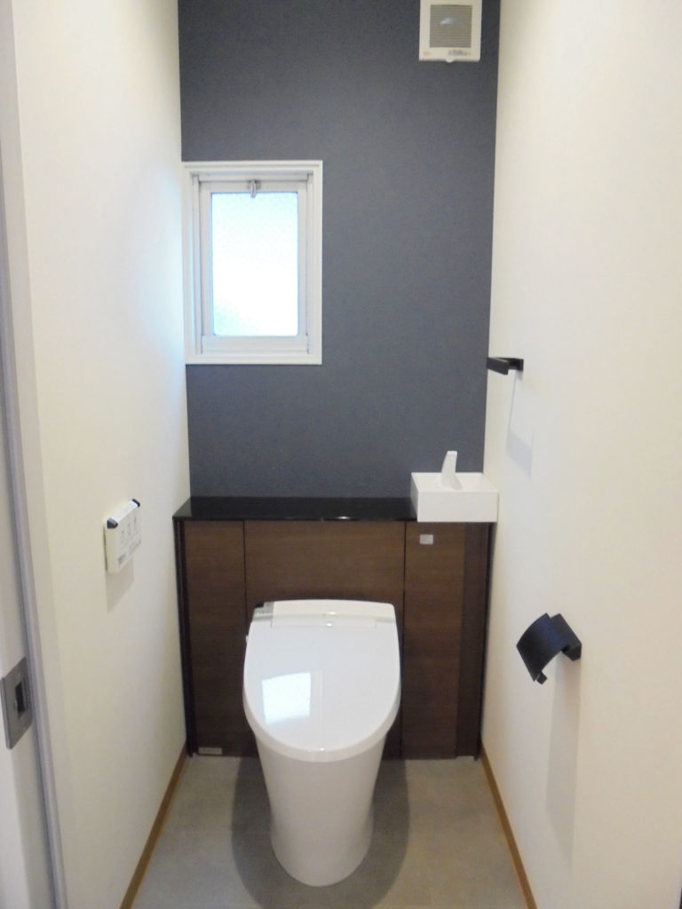 トイレは便器をキャビネット付シャワートイレ一体型のすっきりタイプに交換、ネイビーの壁紙が落ち着いた空間を更に演出しています。