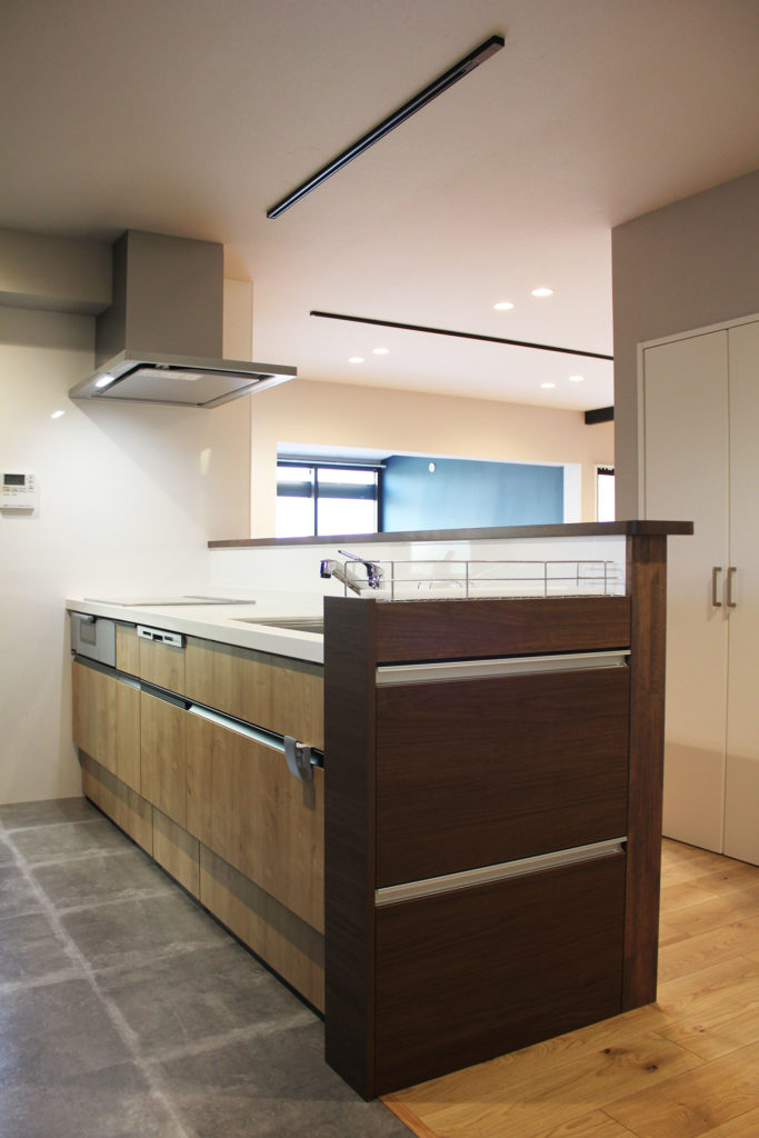 リビングを見ながら作業ができる対面キッチンに。キッチン横収納と腰壁の色合いを合わせ、床は石目調にすることで大人モダンを演出。