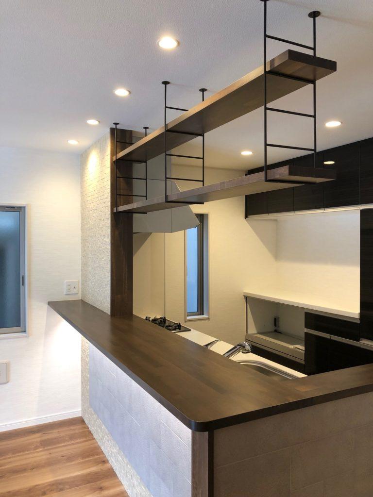 キッチンの腰壁には、LIXILの商品エコカラットをデザイン張りし、対面カウンターとして使えるように幅広くしました。カウンター上にはボトルや小物などが飾れる吊戸棚を設置しました。