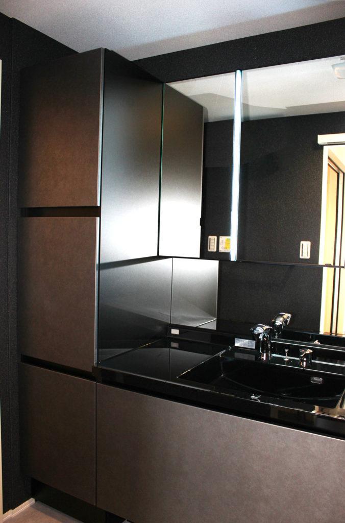 洗面化粧台はLIXILのルミシスを設置しました。大きな鏡と全面ブラックのカウンター、そしてダーク系の壁紙によって、より一層高級感を醸し出しています。