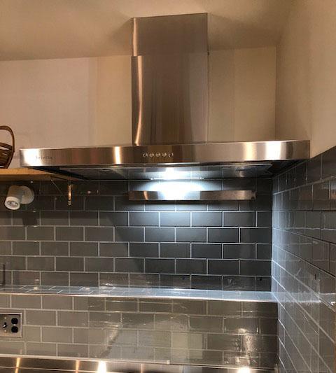 キッチンの壁面はグレーのタイル張りで仕上げました。レンジフードは凛としたフォルムが特徴のベッタです。