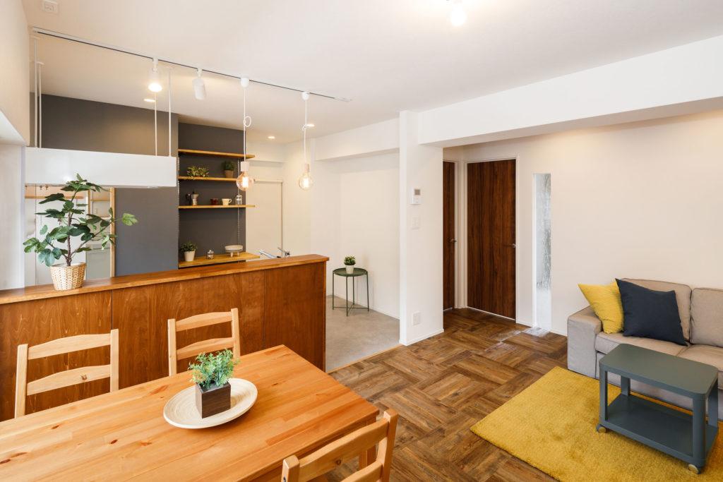 キッチンの腰壁にはシナベニヤを採用し、オイル塗装で趣のあるカラーリングに。リビングの扉や天井にもラフさのある木目素材を使用し、ヴィンテージな雰囲気を演出しています。