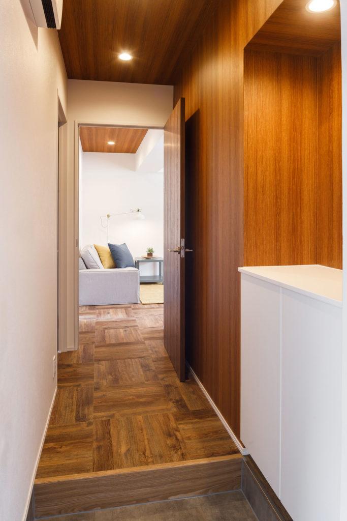 玄関にはモルタル調のタイルを使用しました。天井と壁の一面を木目調の壁紙で仕上げたことで、温かみのある空間を演出しています。