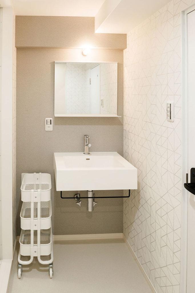 清潔感ある空間にするため、洗面化粧台はサンワカンパニーのレッタンゴロとミラーシェルフを採用しました。幾何学模様とグレーの壁紙を使用し、遊びのある空間へ生まれ変わりました。