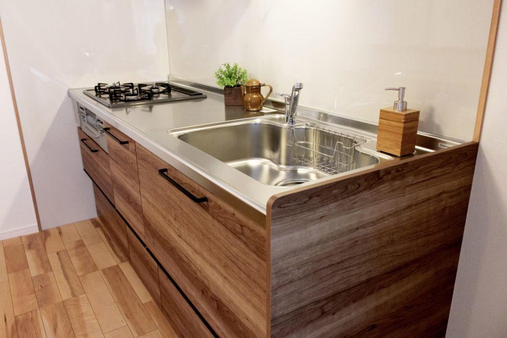 キッチンには軽い力で開き、収納力が高いクリナップのラクエラを採用しました。木目調の扉とブラックの把手がポイントです。