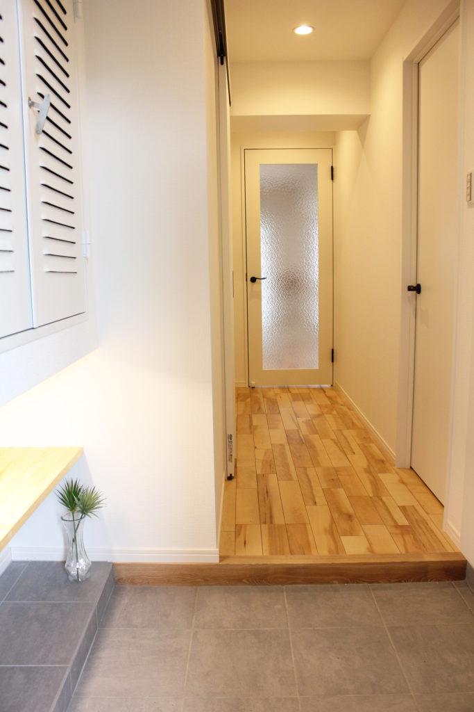 玄関右手には、たっぷり収納できる玄関収納を、左手には靴や物を置きやすいフリースペースを設置しました。間接照明を付けたことでお洒落で使いやすい場所ができました。