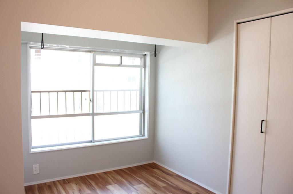 洋室には窓際に室内物干しを設けました。濃いフローリング柄の床とブルーグレーの壁紙で大人っぽくて柔らかい空間に仕上げました。