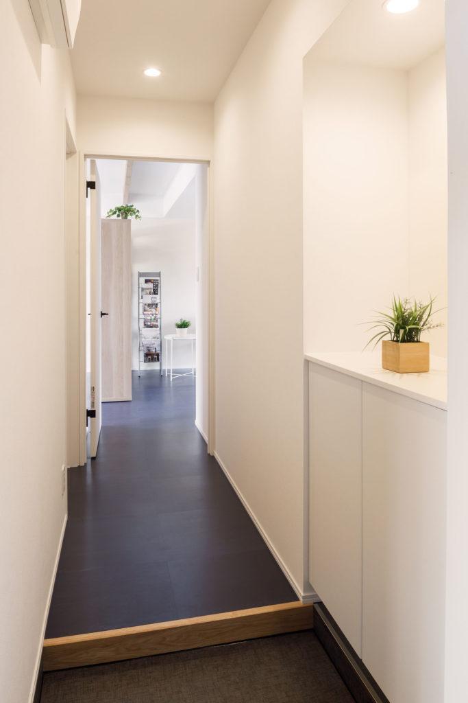 デニム柄の床と合わせ玄関フロアにもデニム柄を取り入れました。玄関ドアやシューズクロゼットは白で揃え、すっきりとした空間を演出しています。
