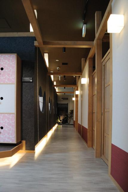 シルバーの木目の床と間接照明、漆黒の壁と飾り窓、反対面の個室の白壁で単調さを無くしました。