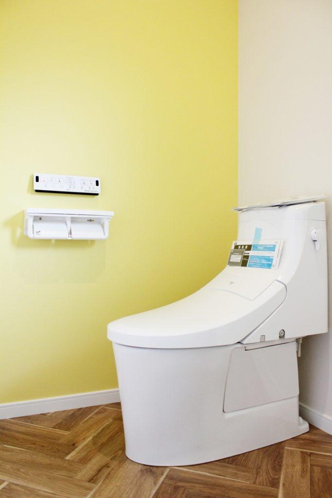 トイレを新設し、ビタミンカラーの黄色をアクセントの壁紙に使用しました。 床はヘリンボーン柄のCFシートに張り替えました。