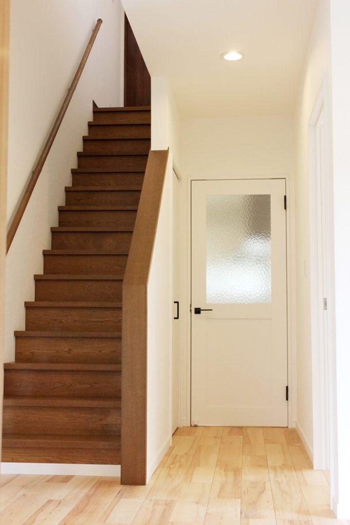 クロスを全面貼り替え、キッチンに繋がる扉はLIXILのラシッサSを採用しました。アンティークガラスがポイントで、玄関ホールと既存階段との色合いが良くとても明るくなりました。