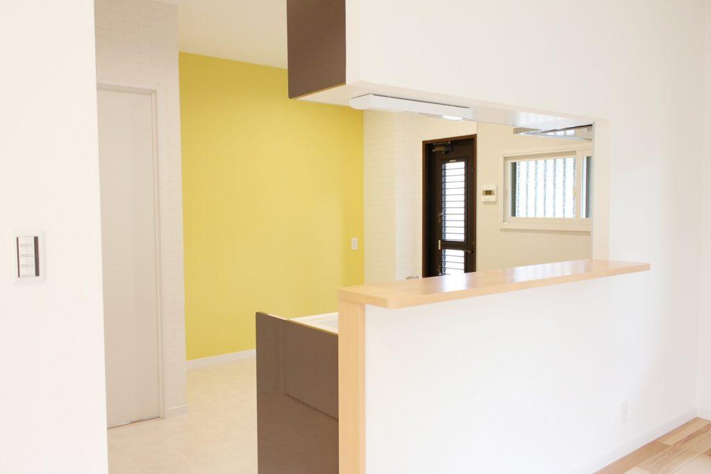 奥様こだわりの黄色い壁紙をキッチンの背面に。元気で明るい印象に生まれ変わりました。使いやすさを考え、笠木を30cmと幅広サイズに変更しました。