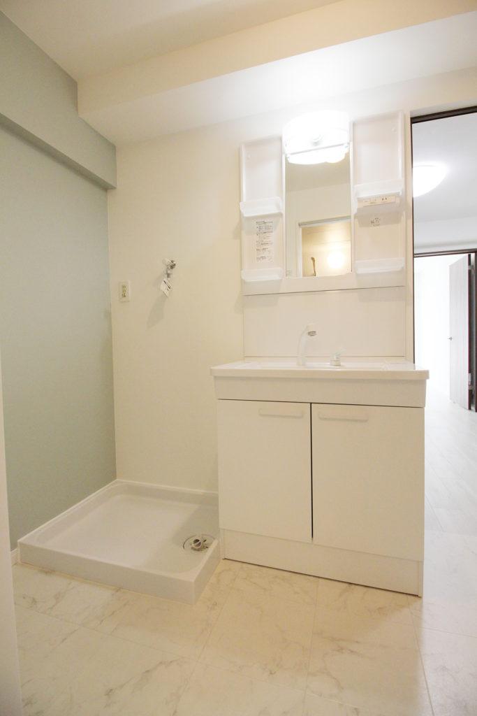 洗面室は出入口の位置を変えたことで以前より入りやすくなりました。床材にはタイル調のCFシートを使い高級感を演出し、アクセントクロスには落ち着いたアースカラーの壁紙を選びました。