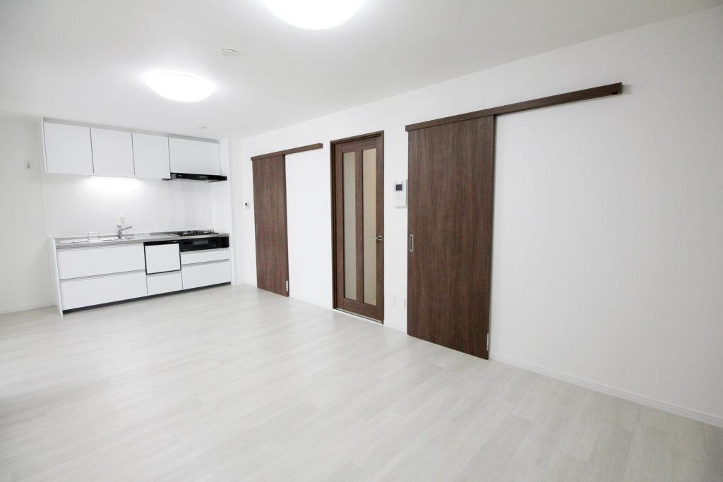 クロスを全面貼り替え、建具はLIXILのラシッサSのクリエモカを採用しました。床にはホワイトオーク柄の塩ビタイルを使用しました。白系の床とブラウンの扉によって空間にメリハリが生まれました。