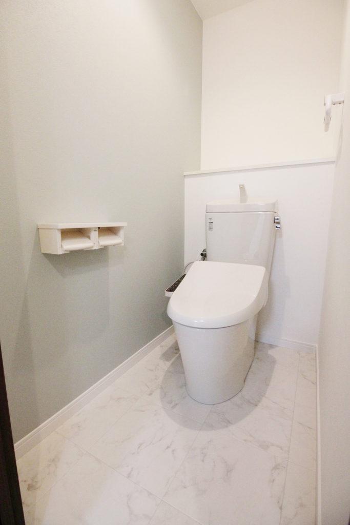 照明を付けても暗い印象だったトイレを一新。白を基調とした明るい空間になりました。洗面室と同じアースカラーの壁紙もポイントです。