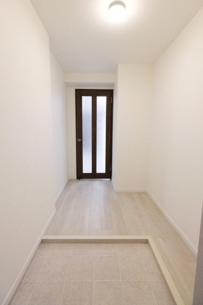元々はブラウンの床で暗い印象でした。今回、全体的に白を使用したことで、ぱっと明るいエントランスが完成しました。玄関ドマには白の石目調床材を使用しました。