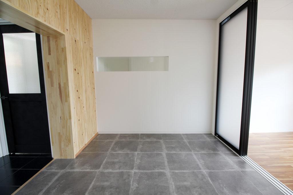 リビングには針葉樹を壁に張り少しだけカジュアルさをプラス。廊下と繋がる壁にはチェッカーガラスをはめ込みました。