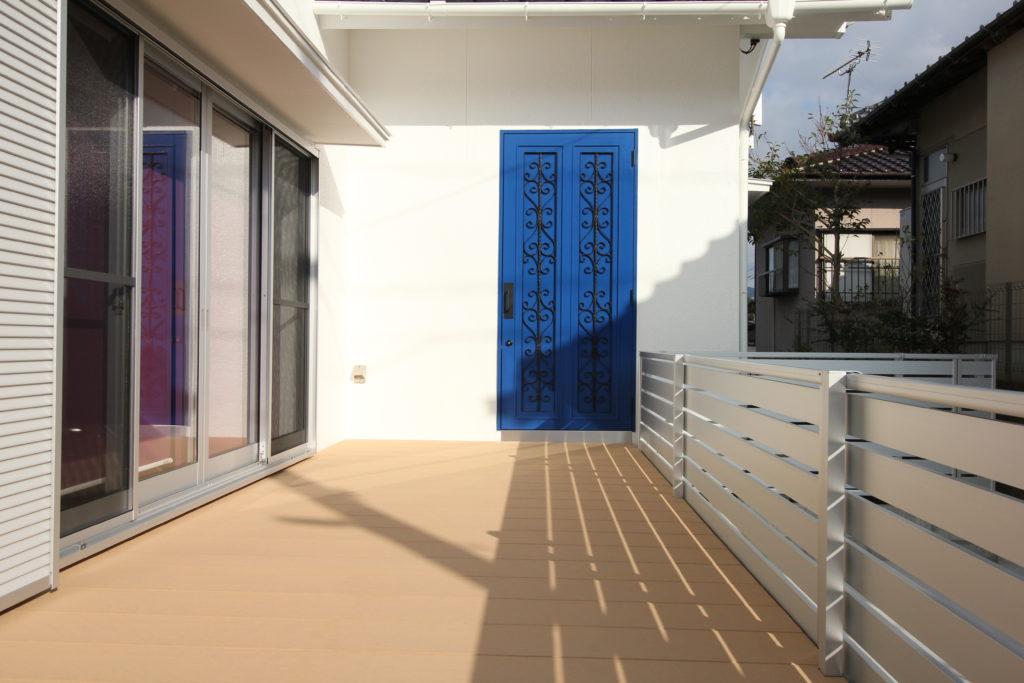 リビングとフリースペースの外部にはYKKapのウッドデッキを新設しました。ロートアイアンをはめ込んだブルーの扉はオリジナルで製作しました。