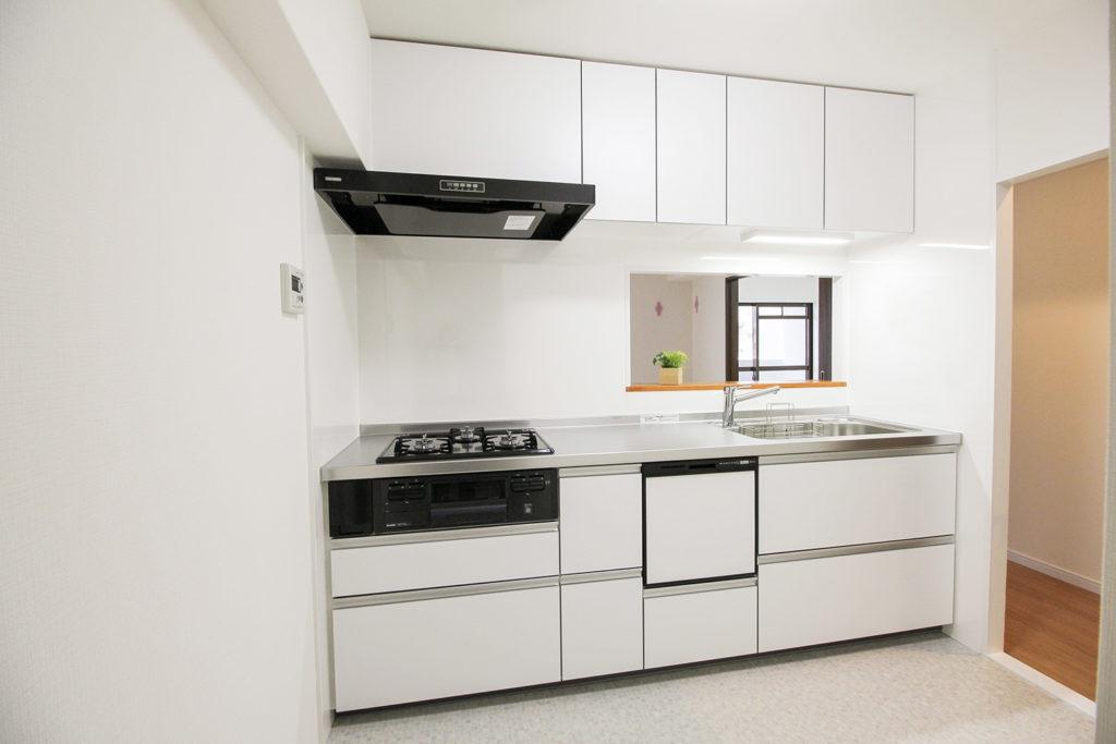キャビネットカラーと合わせ、キッチンは白で統一しました。床にはタイル柄のCFシートを使用しました。背面には冷蔵庫を仕舞えるスペースを確保しました。