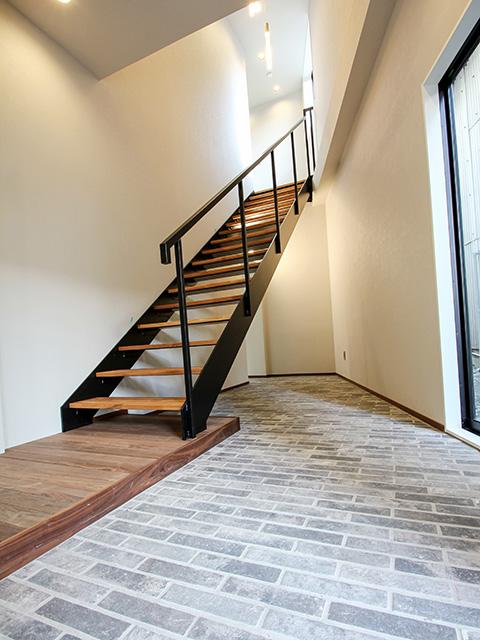 エントランスホールはブリックタイル敷きで、スケルトン階段。石・木・鉄の調和が程よい空間演出です。