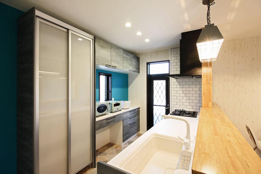 キッチンはクリナップのラクエラを採用しました。サックスオークというグリーン系の色に。背面収納も同色で揃えました。隙間からのぞくブルーの壁紙が良いアクセントになっています。