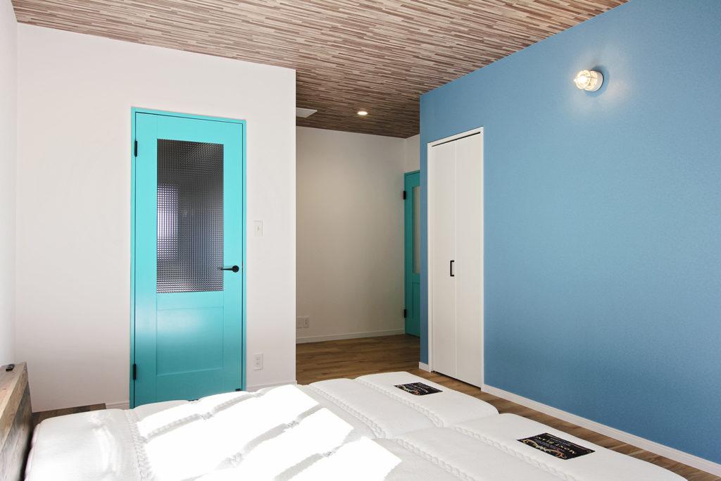 1階の寝室はお庭から差し込む光がとても心地よい一室に。天井は木目調、壁はブルーのクロスを使って、個性がありつつ落ち着いた空間づくりを心がけました。