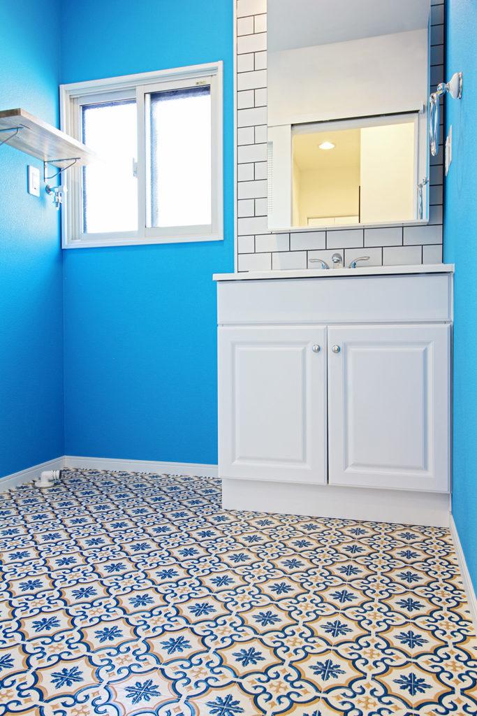 洗面室にはブルーの壁紙を大胆に使用しました。アメリカから輸入した洗面台はお客様こだわり。床はモロッコタイルの床材にしました。