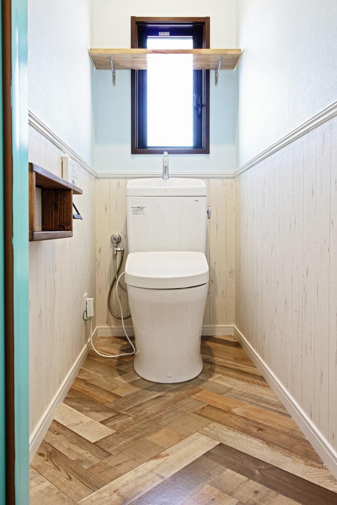 トイレの壁は上下2種類のクロスを使って、白木目調の腰壁を作りました。 見切りには白で塗装したモールディングを設置しました。 床は古材を集めたヘリンボーン風のCFシートを使用しています。