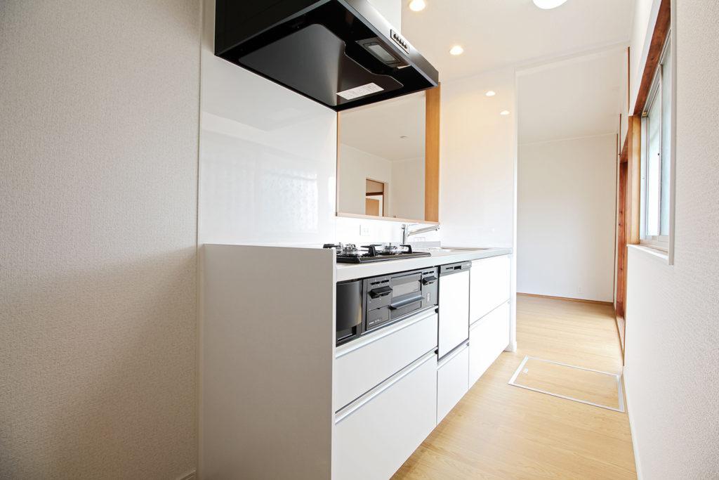 部屋の隅にあったキッチンを真ん中へ移設させました。清潔感ある白の対面式キッチンで家族との食事も楽しくなりそうです。