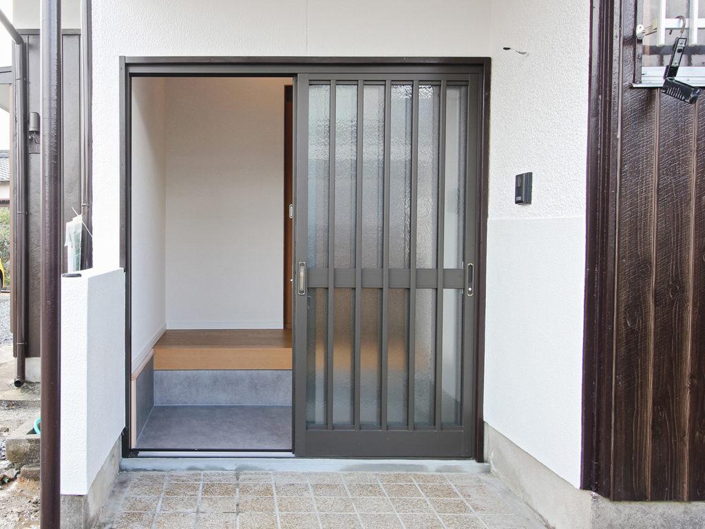 玄関引戸はセキュリティ強化したLIXIL製品に取り替えました。外部はタイル貼りでしたが、モルタルで下地を整えて白で塗装しました。