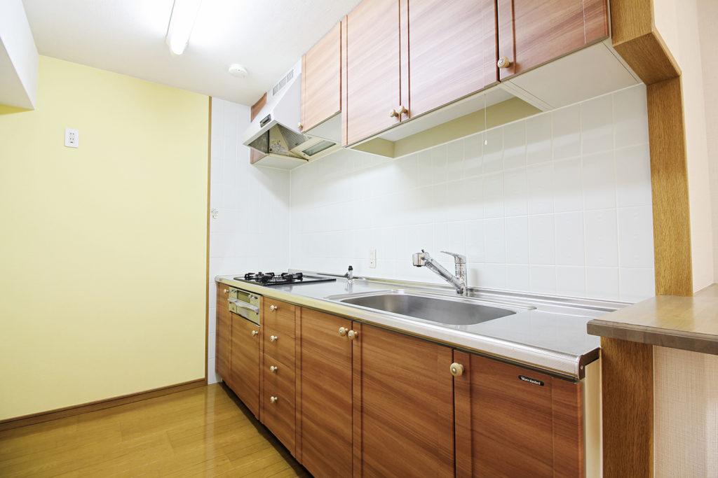 白木目だったキッチンの扉にウォールナット柄のリアテックシートを貼りました。壁紙のアクセントにはイエローの壁紙を選びました。