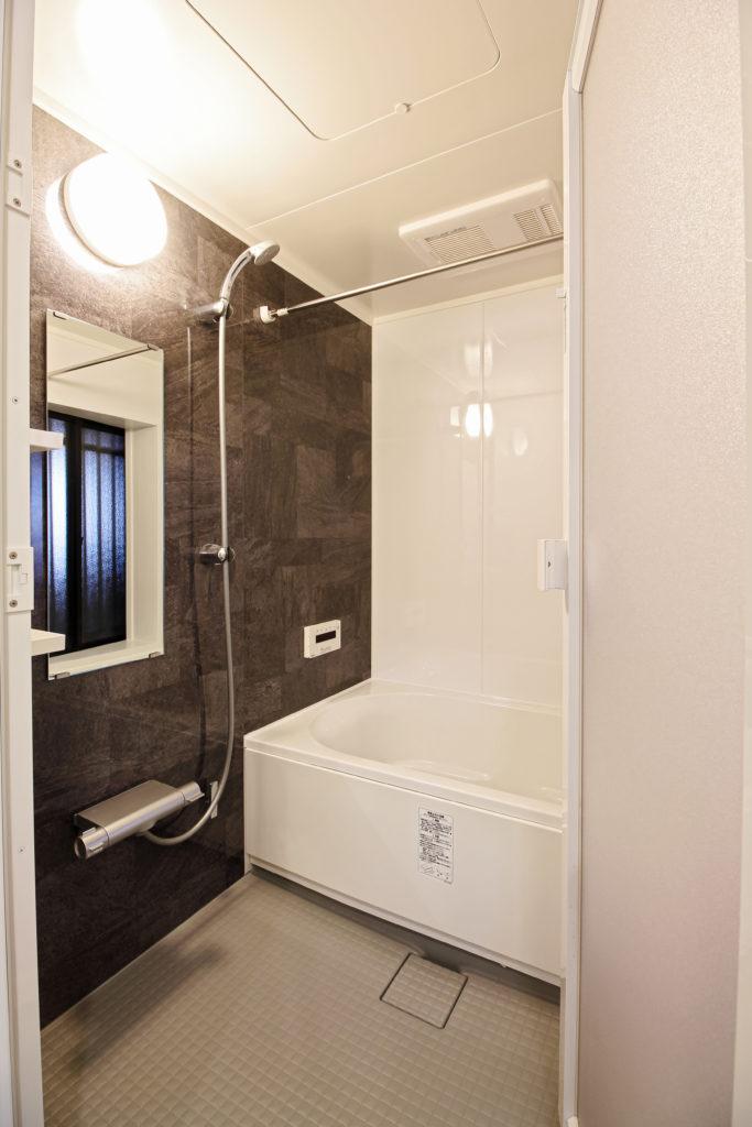 ユニットバスはLIXILのリノビオVを選びました。収納棚や家具に合わせたダークブラウンのアクセントパネルが落ち着いた空間を演出しています。