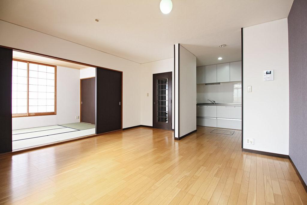 リビングは白を基調として壁紙を貼り替えました。和室の扉はダークブラウンの木目柄の4枚引違い戸に取り替えました。