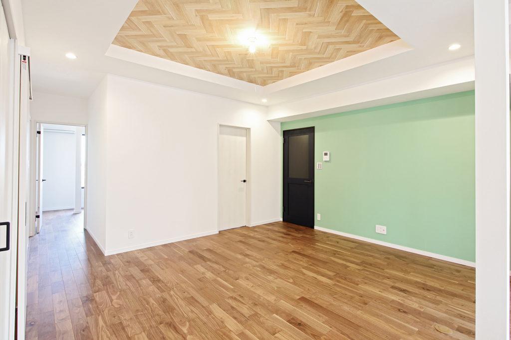 リビングは既存の折上げ天井を活かしたデザインにしました。ヘリンボーンとグリーンの壁紙が心地よいバランスです。白い壁には映画鑑賞ができるようプロジェクター用の壁紙を使いました。