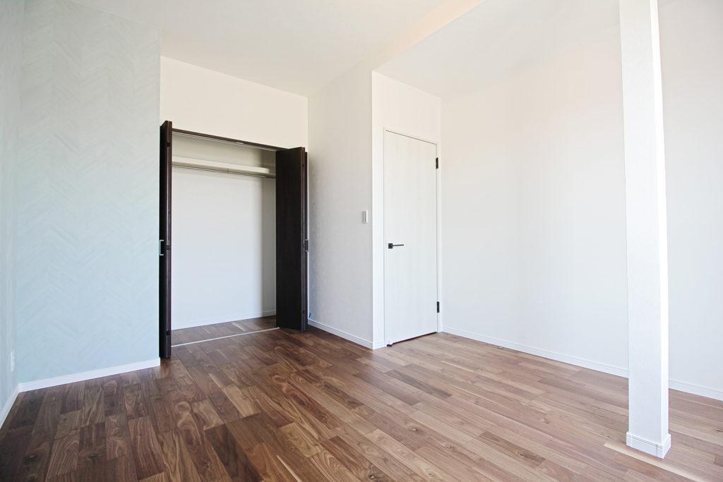 洋室の一面にはアンティークな木質感のあるブルーグリーンの壁紙を使いました。入口は白、クローゼットはダークブラウンとメリハリのある一室に仕上げました。